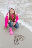 Little girl with drawn heart shape on sand at beach Royalty Free Stock Photography