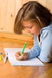 Little girl draws. Little girl is drawing while laying on the floor Royalty Free Stock Photography