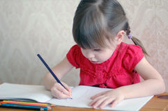 Little girl draws. Girl draws in a notebook Royalty Free Stock Photos