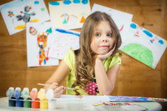 The little girl draws in an album multi-colored paints. The little girl preschool child draws in an album multi-colored paints. Children's drawings royalty free stock images
