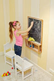 Little girl draws on blackboard Royalty Free Stock Images