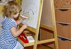 Little girl draws on the Board with colored markers. Young artist. Little girl draws on the Board with colored markers Royalty Free Stock Photos