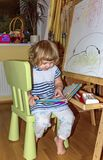 Little girl draws on the Board with colored markers. Young artist. Little girl draws on the Board with colored markers Stock Images