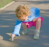 Little girl draws a chalk. The little girl draws a chalk on asphalt in park Royalty Free Stock Image