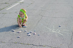 Little girl draws a chalk on asphalt. On a sunny day stock photo