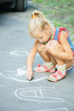 Little girl draws with chalk Stock Image