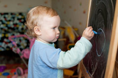 Little girl draws with chalk on a blackboard Stock Images