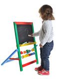 Little girl draws a chalk on a blackboard toy Stock Photo