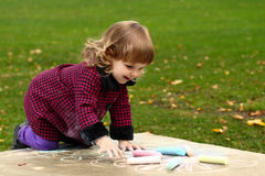 Little girl draws colored chalks standing on her knees Stock Image
