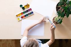 Little girl draws with colored paints on white paper at the table. View from above. Concept of creativity and education royalty free stock photography