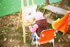 Little girl draws on the easel. stock photo
