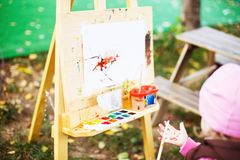 Little girl draws on the easel. royalty free stock photography