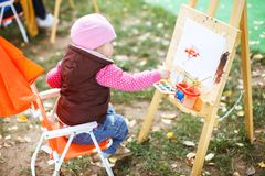 Little girl draws on the easel. royalty free stock image