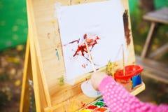 Little girl draws on the easel. stock photos