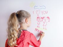 Little girl draws  family with marker on a white board royalty free stock image