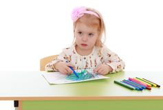 Little girl draws felt pen sitting at the table Stock Photos