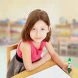 Little girl draws felt-tip pen on a white surface. Stock Photo