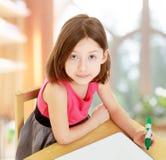 Little girl draws felt-tip pen on a white surface. Stock Photos