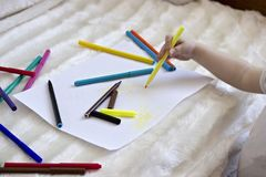 A little girl draws felt-tip pens on a blank sheet, stock image