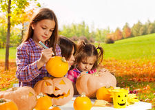 Little girl draws on Halloween pumpkin stock image