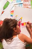 Little girl paints a picture. Little girl draws among her drawings royalty free stock photos