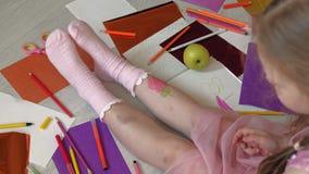 Little girl draws on her feet with felt-tip pens, children`s creativity, development. Beautiful little girl in a pink dress sitting on the floor draws felt-tip stock video footage