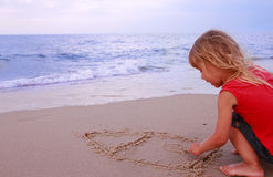 Little girl draws a house by the sea Royalty Free Stock Images