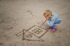 Little Girl Draws In The Sand Stock Photo