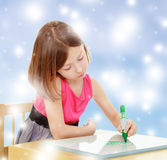 Little girl draws with marker sitting at the table. Stock Photos