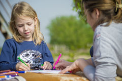 The little girl draws in nature. Royalty Free Stock Image