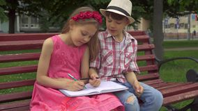 Little girl draws on one page of notebook and her friend on another stock photos