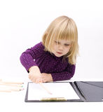Little girl draws in open clipboard with crayons Stock Photo