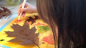 Little girl draws and paints details of the autumn application stock footage