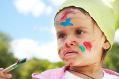Little girl draws paints. On a green lawn Royalty Free Stock Photography