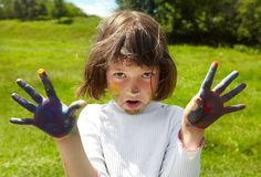 Little girl draws paints. On a green lawn Stock Photography