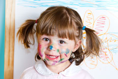 Little girl draws paints. Smiling little girl draws paints stock photography