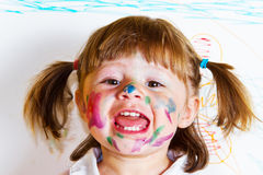 Little girl draws paints. A smiling little girl draws paints stock image