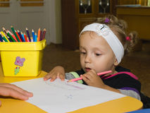 Little girl draws pencil on paper Stock Photography