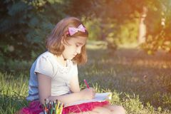 Little girl draws sitting on the grass royalty free stock photo