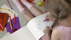 Little girl draws with pencils, children`s creativity, development. Beautiful little girl in a pink dress sitting on the floor draws with pencils and felt-tip stock video