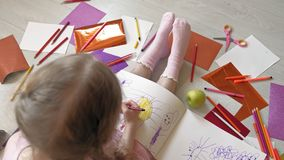 Little girl draws with pencils, children`s creativity, development. Beautiful little girl in a pink dress sitting on the floor draws with pencils and felt-tip stock video footage