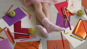 Little girl draws with pencils, children`s creativity, development. Children`s creativity, drawing. the little girl is lying on the floor, her legs are close up stock video