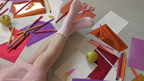 Little girl draws with pencils, children`s creativity, development. Children`s creativity, drawing. the little girl is lying on the floor, her legs are close up stock footage