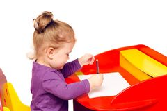 Little girl draws with pencils sitting at a red table Stock Image