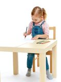 Little girl draws pencils sitting at the table. Stock Images