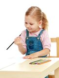 Little girl draws pencils sitting at the table. Stock Photography