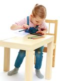Little girl draws pencils sitting at the table Stock Photo