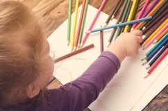 Little girl draws with pencils on a wooden table Royalty Free Stock Photography
