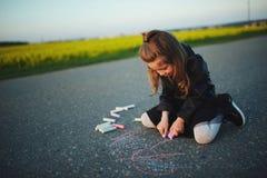 Little girl draws pictures on asphalt. Little happy girl draws pictures on asphalt Stock Photography