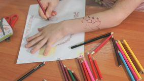 Little girl draws the pictures using color pencils stock video